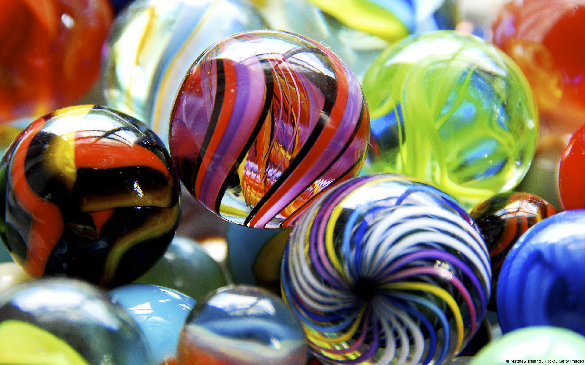Close-up shot of brightly colored glass marbles of varying designs, including classic cat's eye, swirling rainbow patterns, and twisting, psychedelic shapes and colors